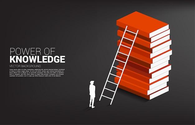 Silhueta do homem de negócios pronto para mover-se para a parte superior da pilha de livro com escada.