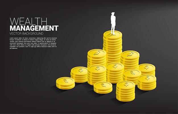 Silhueta do homem de negócios que está sobre a pilha de moeda.