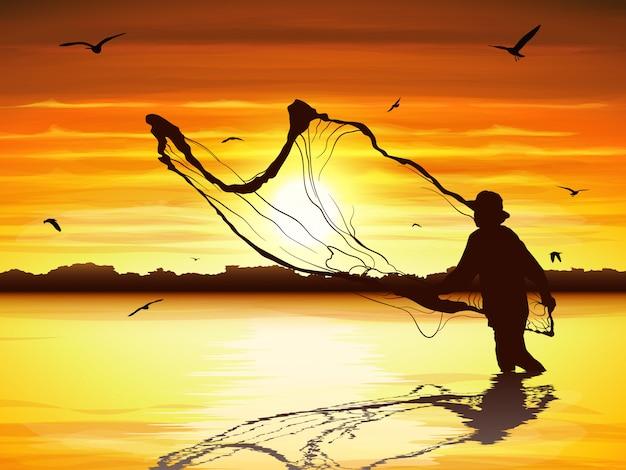 Silhueta do homem que trava o peixe no crepúsculo.