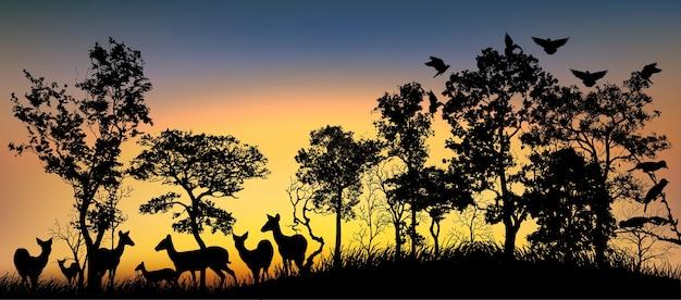 Silhueta negra de árvores e animais.