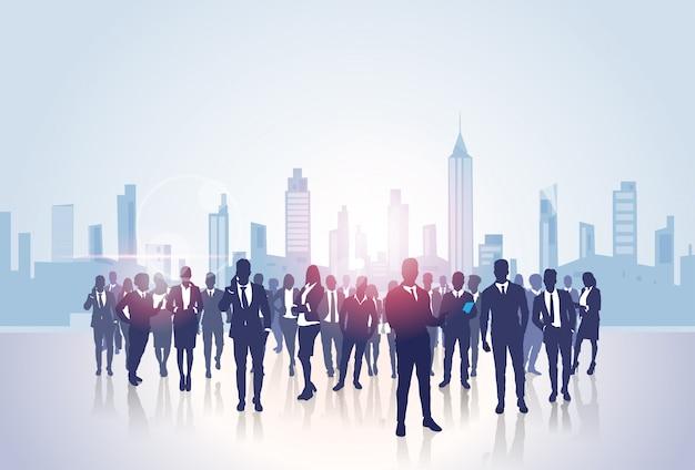 Silhuetas de grupo de pessoas de negócios sobre a cidade edifícios de escritórios modernos de paisagem
