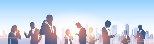 Silhuetas de grupo de pessoas de negócios sobre a cidade paisagem moderna escritório rede social de comunicação