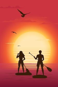 Silhuetas de homem e mulher em pé na prancha de remo, tendo como pano de fundo o sol poente