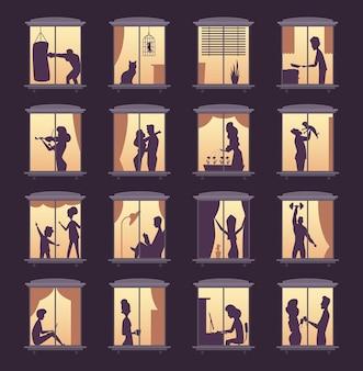 Silhuetas de janela de pessoas. iluminação em edifícios de apartamentos de torre de casas noturnas com silhuetas de pessoas