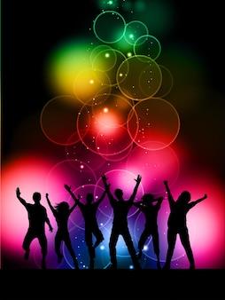 Silhuetas de pessoas dançando em um fundo de luzes coloridas de bokeh