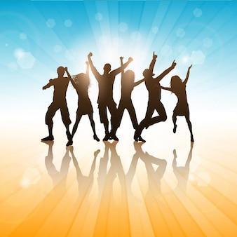 Silhuetas de pessoas dançando em um fundo do verão