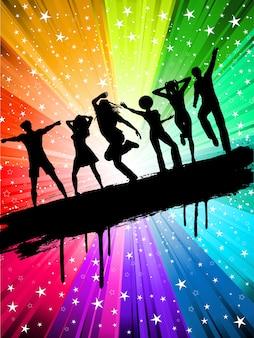 Silhuetas de pessoas dançando em um fundo multi colorido estrelado