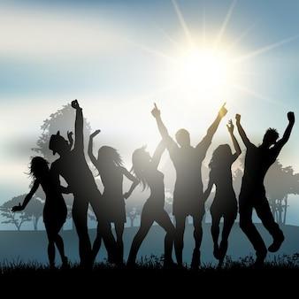 Silhuetas de pessoas dançando no campo