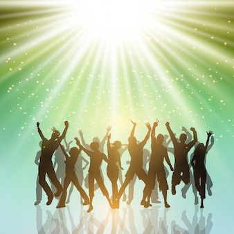 Silhuetas de pessoas do partido que dançam em um fundo do starburst