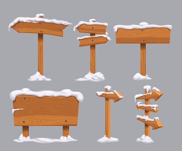 Sinais direcionais de madeira com neve