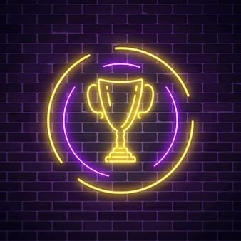 Sinal de néon brilhante com copo de prêmio em moldura redonda no fundo da parede de tijolo escuro. troféu honorário da taça dos vencedores