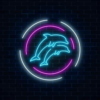 Sinal de néon brilhante de dois golfinhos pulando em quadros de círculo no fundo da parede de tijolo escuro.