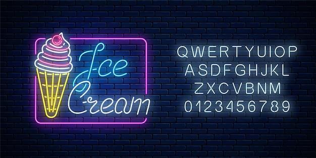 Sinal de néon brilhante de sorvete com cereja e alfabeto na parede de tijolo escuro.