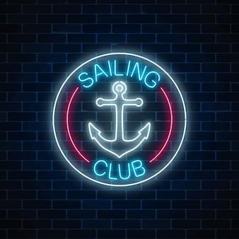 Sinal de néon brilhante do clube à vela com símbolo de âncora em quadros de círculo no fundo da parede de tijolo escuro.