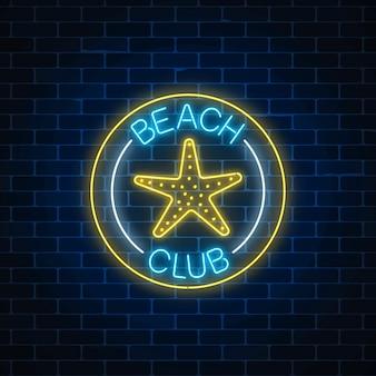 Sinal de néon brilhante do clube de praia de recreação com símbolo de estrela do mar em quadros de círculo no fundo da parede de tijolo escuro.