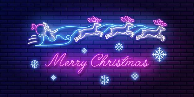 Sinal de néon com letras de feliz natal com papai noel e o time de renas e flocos de neve na parede de tijolos