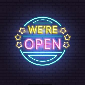 Sinal de néon 'estamos abertos' na parede de tijolos