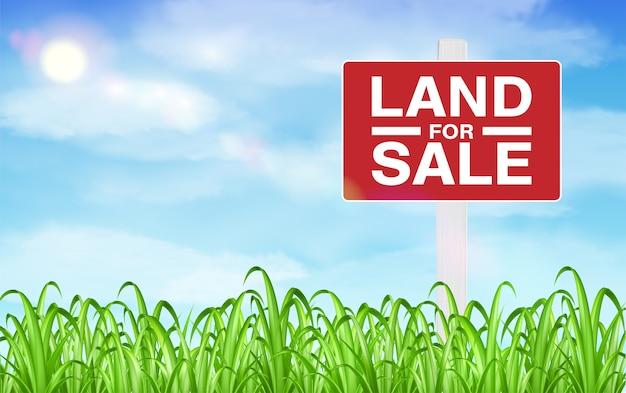 Sinal de venda de terra no campo de grama com fundo do céu