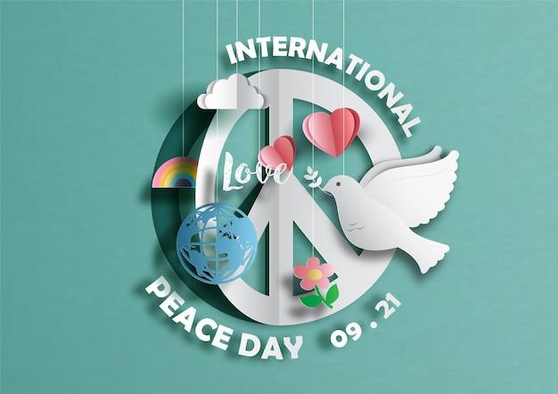 Sinal e símbolos do dia internacional da paz em estilo de corte de papel sobre fundo verde