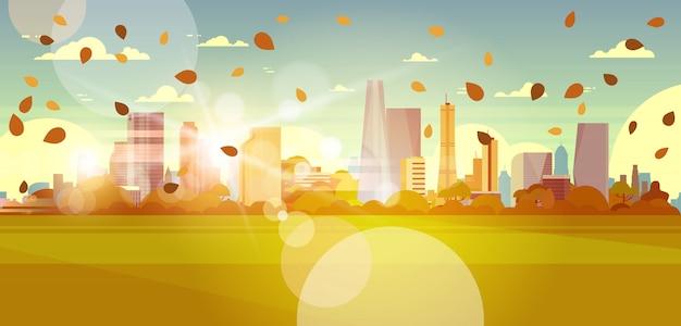Skyline de paisagem urbana de outono com folhas voando na luz solar sobre o conceito de paisagem urbana de edifícios de arranha-céus