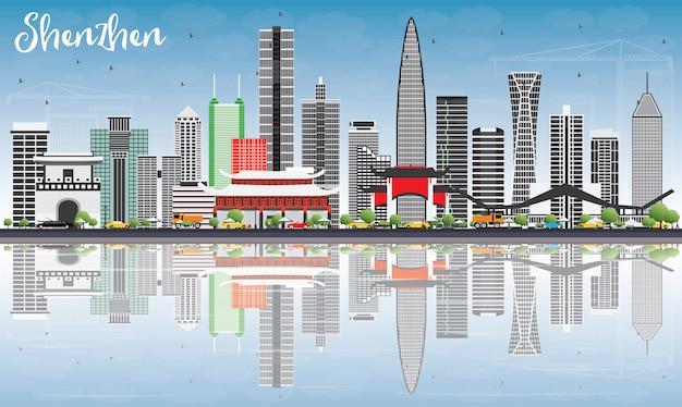 Skyline de shenzhen com edifícios de cinza, céu azul e reflexões.