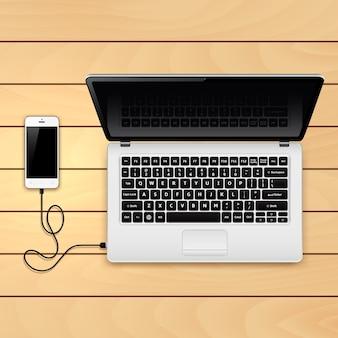 Smartphone conectado ao laptop na mesa de madeira