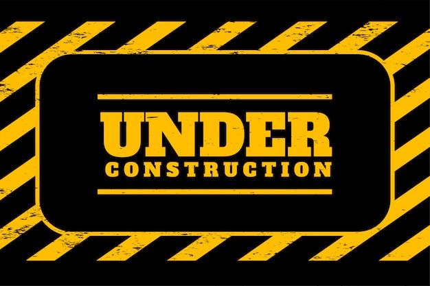 Sob fundo de construção em listras amarelas e pretas