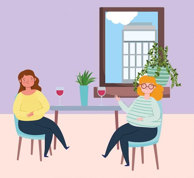Social distanciando restaurante ou um café, mulheres jovens com copo de vinho mantêm distância