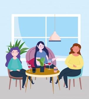 Social distanciando um restaurante ou um café, as mulheres jovens sentadas à mesa mantêm distância
