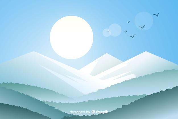 Sol e pássaros ao longo de uma cadeia de montanhas