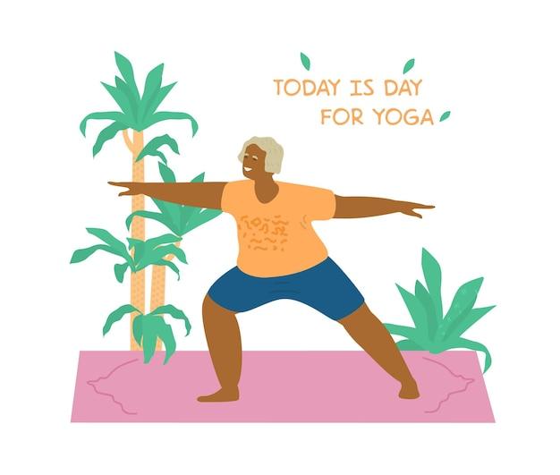 Sorridente senhora afro-americana praticando ioga na esteira de ioga rodeada de plantas. mulher idosa em pose de guerreiro.