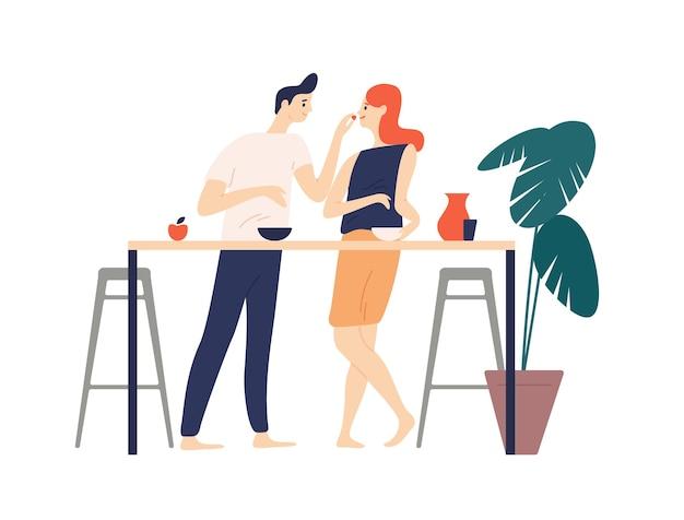 Sorrindo, homem e mulher em pé na cozinha, comendo lanches e alimentando um ao outro. menino e menina felizes tomando café da manhã e almoço. casal fofo curtindo comida juntos
