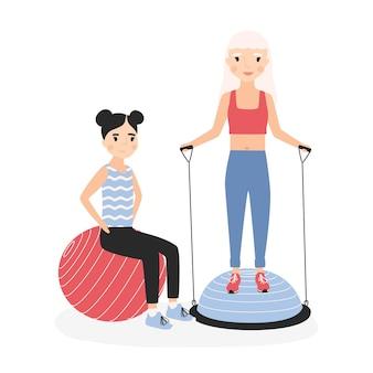 Sorrindo, mãe e filha realizando exercícios aeróbicos com bolas de ginástica.