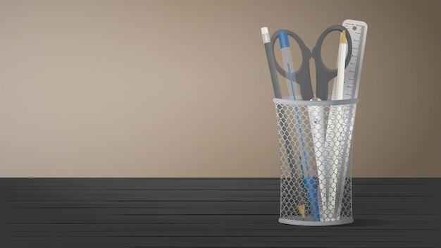 Suporte de metal para canetas em cima da mesa. vidro para papelaria. lápis, canetas, régua de metal, tesoura em um suporte de metal.
