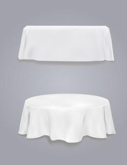 Tabela com toalha de mesa em um fundo cinzento.