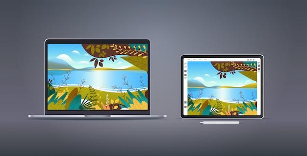 Tablet gráfico e laptop com papéis de parede de belas paisagens em telas na parede cinza