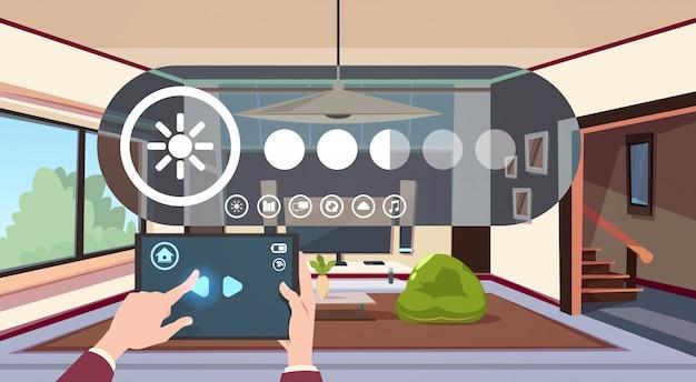 Tabuleta de digitas do uso da mão com automatização esperta home do app sobre a tecnologia moderna interior da sala de visitas do conceito da monitoração da casa