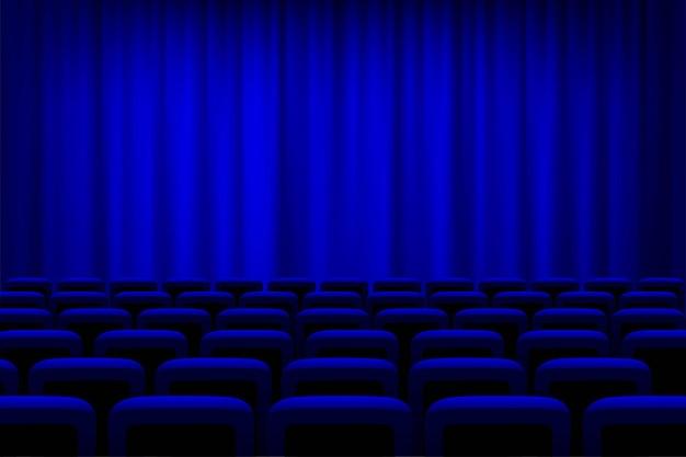 Teatro com cortinas azuis e fundo de assentos, auditório de cinema vazio.