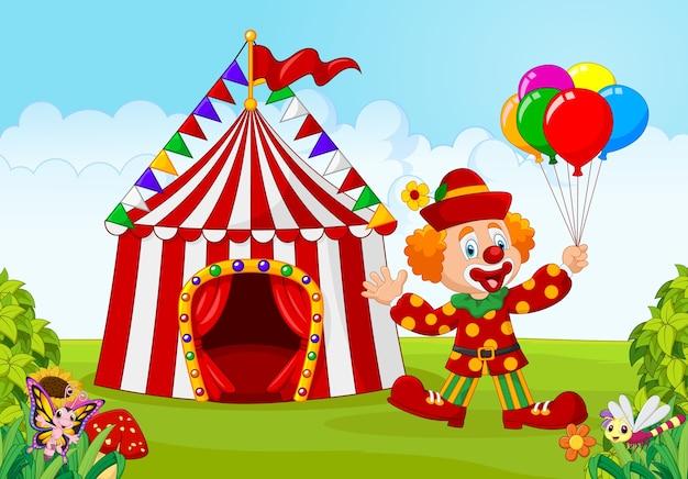 Tenda de circo com palhaço segurando balão no parque verde