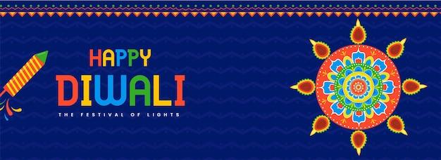 Texto colorido de diwali feliz com rangoli ou mandala decorada com lâmpadas de óleo aceso (diya) e foguetes de fogos de artifício sobre fundo de linhas em zigue-zague azul.