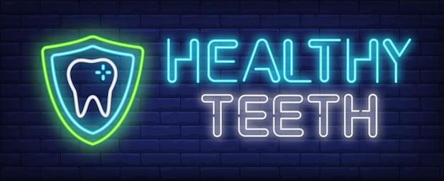 Texto de dentes saudáveis neon e dente com escudo de proteção