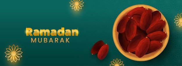 Texto dourado de ramadan mubarak com vista superior da tigela de datas no fundo verde padrão árabe.