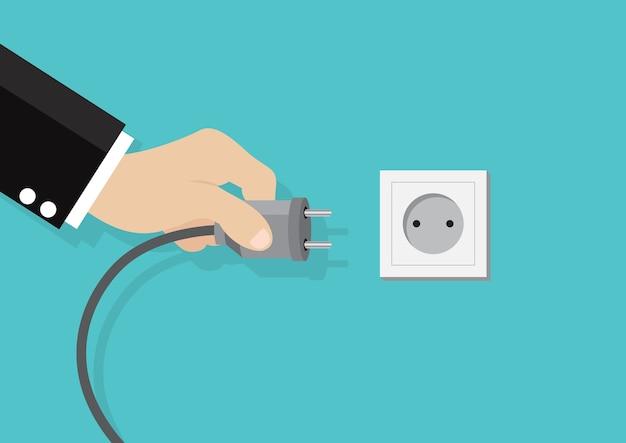 Tomada de energia elétrica segurando na mão.