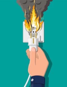 Tomada elétrica com ficha em chamas. sobrecarga de rede. curto circuito. conceito de segurança elétrica. tomada de parede em chamas com fumaça. ilustração vetorial em estilo simples