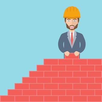 Trabalhador da construção civil fazendo parede de tijolos