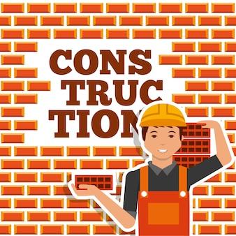 Trabalhador da construção civil segurando tijolo e parede