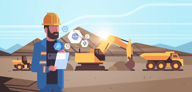 Trabalhador de homem a céu aberto no capacete usando escavadeira de aplicativo móvel