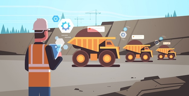 Trabalhador de homem a céu aberto no capacete usando o aplicativo móvel para controlar caminhões basculantes
