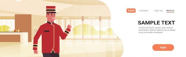 Trabalhador masculino feliz bellman no conceito uniforme de serviço de hotel personagem de desenho animado interior lobby área moderna recepção