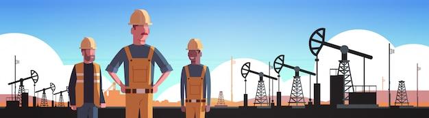 Trabalhadores de uniforme laranja trabalhando no equipamento de perfuração para a bomba pumpjack produção de petróleo comércio indústria petróleo conceito retrato horizontal